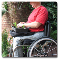 Fred sits in his wheelchair, using the Trabasack on his lap to pot flowers in his garden