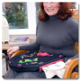 Bernie sits in a high-back chair, using the Trabasacking Curve Connect pink trim to aid crafting with thread