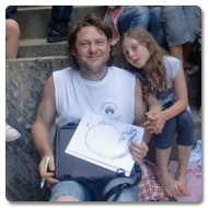 Brian sits outdoors on stone steps, smiling to the camera, he is surrounded by lots of local children whilst he illustrates drawings on using his Trabasack lap desk