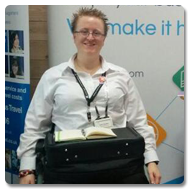 Ruth sits in her wheelchair, smiling to the camera with a Trabasack Max and book on her lap, behind her is a large display for Virya Group Ethical Technology Solutions