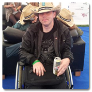 Mark is sitting in a wheelchair with a wry expression, he is wearing a Cowboy-style straw hat, placing a can of beer on the tray surface of the Trabasack Mini on his lap