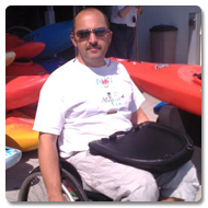 Alan looks straight to the camera, he is sitting in a wheelchair with a Trabasack Curve on his lap, behind him are canoes lined-up ready to be used