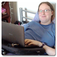 Danni is lying in bed, propped-up with cushions, she smiles to the camera whilst using her laptop on the Trabasack lap desk