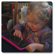 A toddler girl with blonde hair concentrates on using a tablet pc on top of a Curve Connect