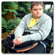 Warren is a young man with brown hair, he is sitting in his wheelchair with Trabasack on lap, surrounded by tropical plants
