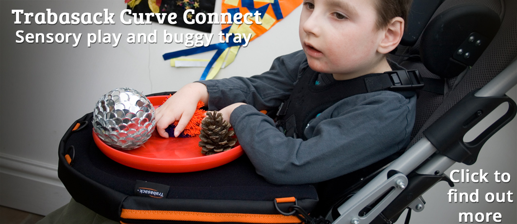 Photographic image of a young boy in a specialist buggy, playing with sensory items on the Curve Connect