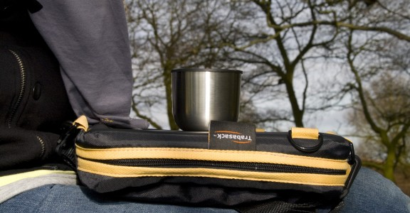 Photo of Trabasack Mini on someone's lap with a cup on top, behind in the background is a forrest of trees
