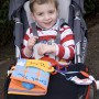 Young boy smiles to the camera whilst sitting in his buggy, with a Trabasack Curve Connect play tray on his lap