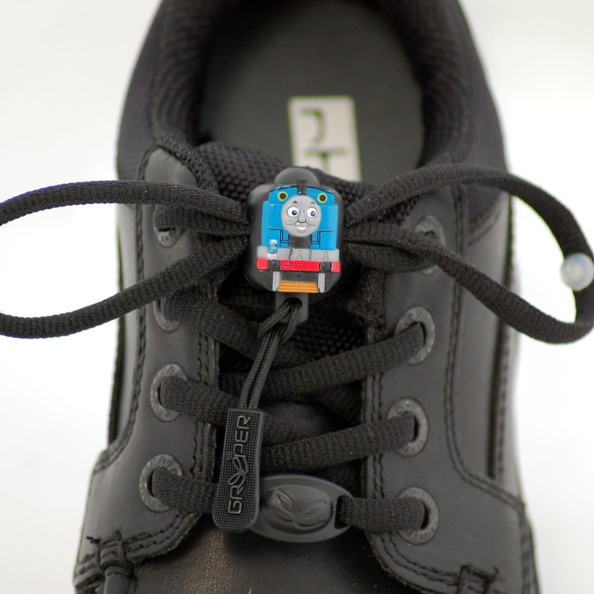 Photograph of a smart, black shoe with black Greeper laces which feature a small Thomas the Tank Engine motif in the centre