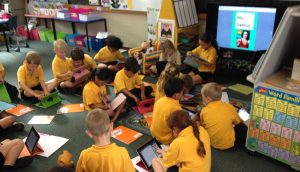 Children on the floor with iPads using tech for education