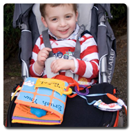 Victor sits in his buggy, smiling to the camera, with a Trabasack on his lap with books and toys attached to it