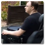 A man wearing a black t-shirt, with brown hair and glasses, is pictured moving down a suburban street in a powerchair, with a Trabasack Curve on his lap