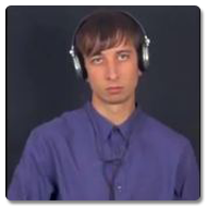 Steven wears a purple shirt, looks to the camera with a dead-pan expression, whilst pressing a button on his Korg which is mounted on a Trabasack Curve Connect