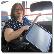 Eleanor looks towards the camera, holding a Trabasack Max in her hands, whilst riding on a bus
