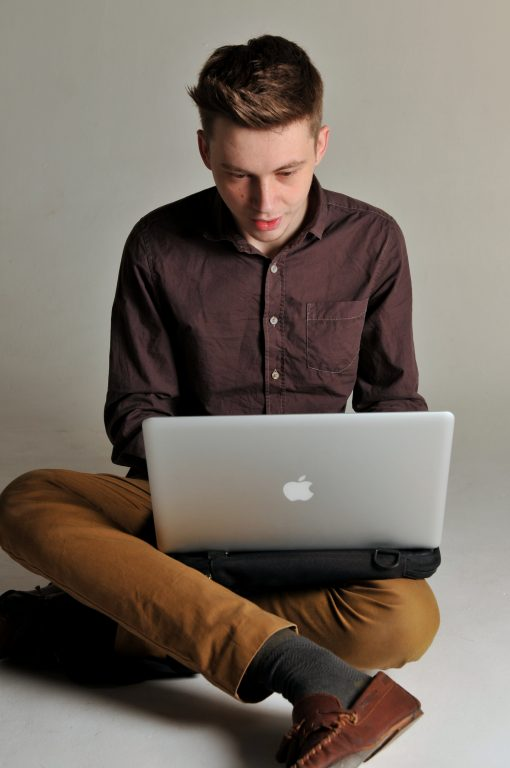 Young man sitting on the floor using the Trabasack Mini on his lap with a laptop