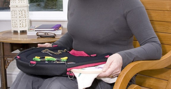 Image of a lady in a high-back chair using the Trabasack Curve Connect as a craft tray