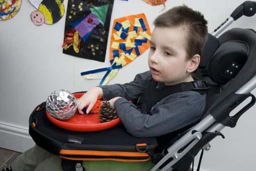 Image of young boy in a buggy playing with sensory items on a Trabasack Curve Connect play tray