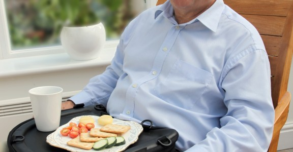 An elderly gentleman sits in a high-back chair, eating lunch using the Trabasack Curve as a lap tray