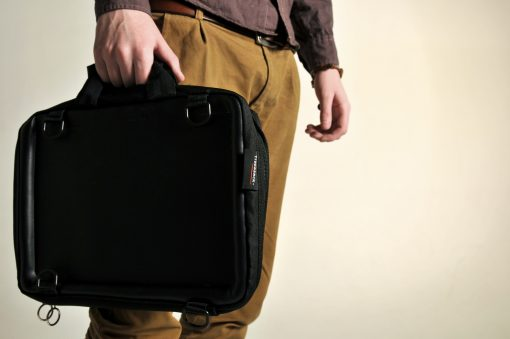 Image of a young man carrying the Trabasack Mini in hand as a briefcase