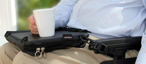 Image of an elderly gentleman sat in a wheelchair resting a cup upon the tray surface of his Trabasack curve