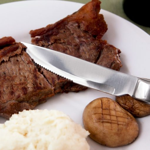 Photograph shows a plate of food with potatoes and steak, with the Knork Steak Knife cutting through the steak