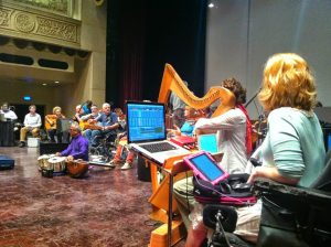 harp and other instruments seen in an orchestra, wheelchair user has a tablet and a makes music using the trabasack curve connect as a tray