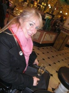 Inventor Clare Edwards with a glass of champagne in Harrods food hall using a trabasack food tray for a wheelchair.