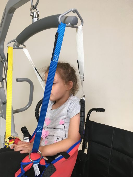 Image shows a photograph of the side view of a young girl sat in the ProMove transfer sling attached to a spreader bar hoist