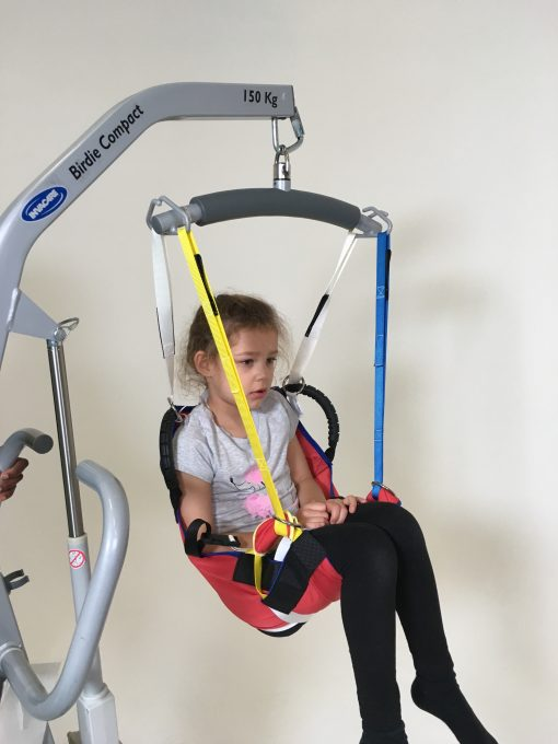 Image shows a photograph of a young girl being cradled in a ProMove Sling attached to a spreader bar hoist