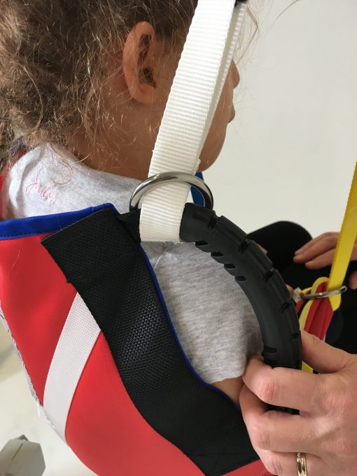 Image shows a photograph of the back, rear shoulder view of a young girl sitting in a ProMove sling with the hoist straps being attached