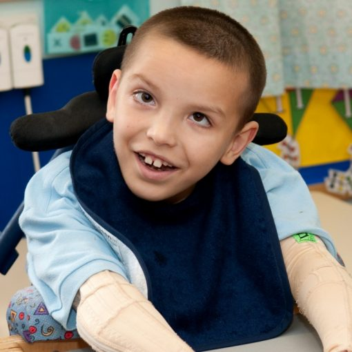 Image shows a photograph of a seated young boy wearing a light blue top and a navy blue dribble bib