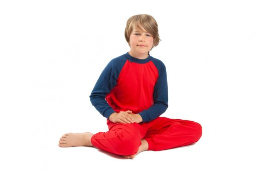 Image shows a photograph of a young boy sitting on the floor with knees bent to the side, hands on his lap, wearing a red and navy blue sleepsuit