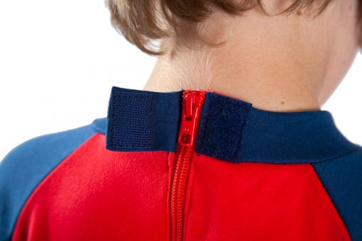 Image shows a photograph of the back of a boy's neck and shoulders, to illustrate the opening of the velcro cover for the hidden zip on the back of a Seenin sleepsuit in navy and red