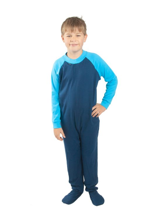Image shows a photograph of a young boy stood facing the camera, with one hand on his hip wearing a navy blue and turquoise, footed all-in-one sleepsuit.