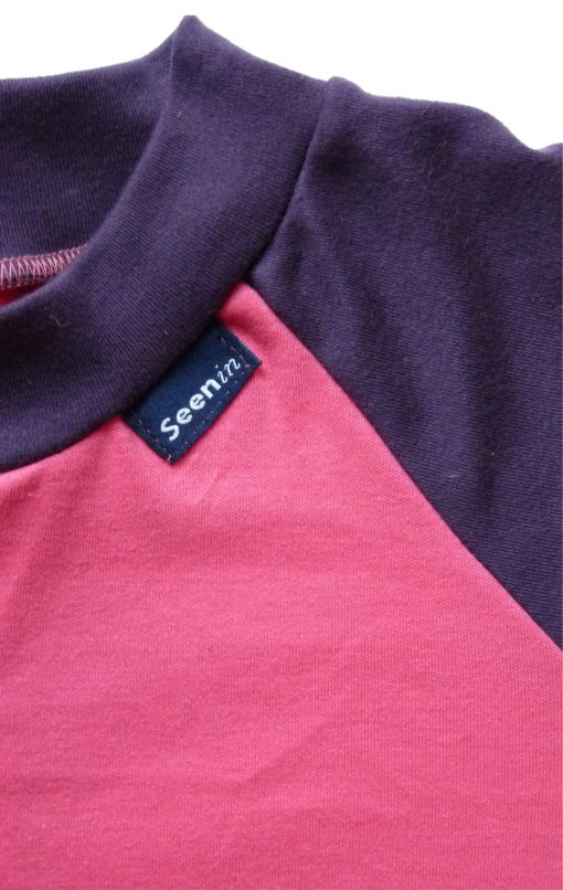 Image shows a photograph of a close-up of the collar and chest area of a Seenin sleepsuit in pink and purple