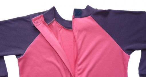 Image shows a photograph of the back of a Seenin sleepsuit in pink and purple, with the back neck area open and unzipped