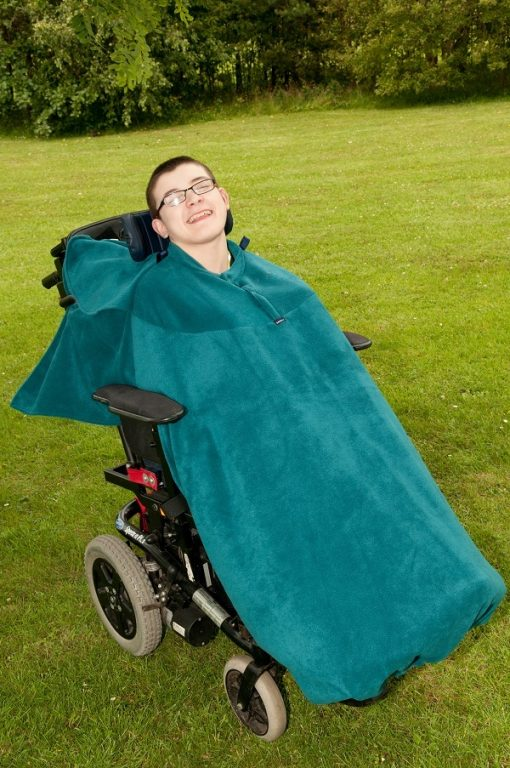 Image is a photograph of a young man smiling, sitting in a wheelchair outdoors with a teal full cover fleece