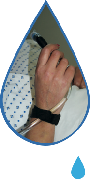 Image is a photograph cut-out in a tear-drop shape, showing a close-up of a patient wearing a hospital gown, with the drinking tube of the Water Drop attached to the side of their hand using a velcro strap, accessing water to drink