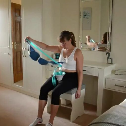 Image is a photograph of a woman sat on a stool in a bedroom whilst using the BraBuddy to fit a bra