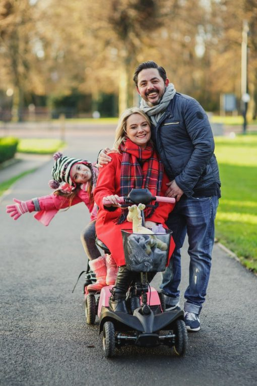 Image is a photgraph of a family of mum, dad and daughter outdoors with mum sat on a mobility scooter, dad standing close and smiling, and daughter sat behind on a Skoe Hitch with her head titled smiling at the camera.