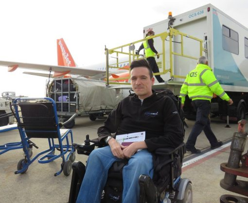 Image is a photograph of easyTravelseat founder Josh Wintersgill sat in a easyTravelchair within his wheelchair on the apron or tarmac of an airport with an easyJet plane and staff behind him