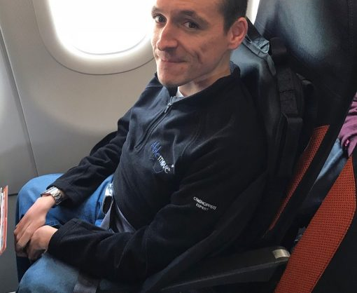 Image is a photograph of easyTravelseat founder Joish Wintersgill sat smiling in an easyTravelseat on an aircraft