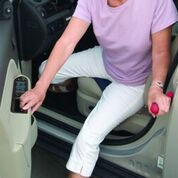 Image is a photograph of an older lady alighting from the passenger-side of a car using the Handy Bar as an aid