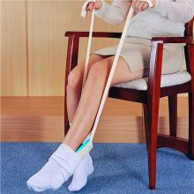 Image is a photograph of the lowerhalf of a woman seated in a dining chair using the Deluxe Sock Aid to put-on a pair of white socks